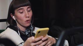Портрет молодой стильной женщины в наушниках слушая музыку и просматривая на мобильном телефоне публично транспортирует r акции видеоматериалы