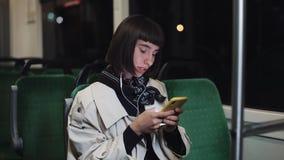 Портрет молодой стильной женщины с наушниками слушая музыку, используя смартфон, поет и смешные танцы публично акции видеоматериалы
