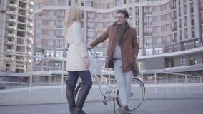 Портрет молодой счастливой пары в любов усмехаясь и связывая с положением велосипеда на предпосылке a акции видеоматериалы