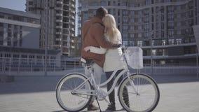 Портрет молодой счастливой пары в любов усмехаясь и связывая с положением велосипеда на предпосылке a видеоматериал