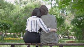 Портрет молодой счастливой пары в случайных одеждах тратя время совместно в парке, имеющ дату Любовники сидя дальше видеоматериал