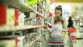 Портрет молодой счастливой семьи в супермаркете Милая маленькая девочка сидит в магазинной тележкае, молодой женщине выбирает видеоматериал