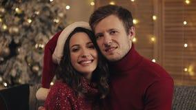 Портрет молодой счастливой семьи сидя на софе около рождественской елки дома Пары празднуя Новый Год смотря сток-видео