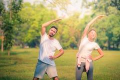 Портрет молодой тренировки пар для здоровья в парке на заходе солнца Спорт и любовь концепции r стоковое изображение
