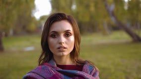 Портрет молодой уверенной девушки смотрит камеру в солнечном парке видеоматериал