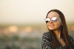 Портрет молодой усмехаясь девушки в солнечных очках с отражательными стеклами Стоковое Фото
