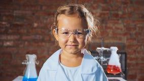 Портрет молодой усмехаясь девушки ребенка ученого в химической лаборатории стоковые фото