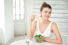 Портрет молодой усмехаясь женщины есть свежий салат в белой комнате Стоковые Изображения RF