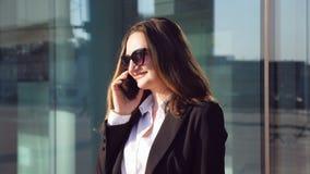 Портрет молодой усмехаясь коммерсантки говоря на телефоне Счастливая красивая женщина говоря на smartphone около современного акции видеоматериалы