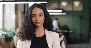 Портрет молодой успешной коммерсантки на занятом офисе Красивый женский работник смотря камеру и делая большие пальцы руки акции видеоматериалы