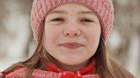 Портрет молодой школьницы с веснушками в древесинах в зиме Он греет его руки в mittens и прикладывает их к сток-видео