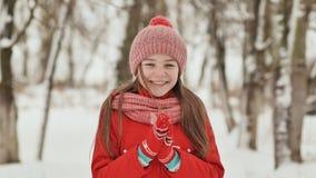 Портрет молодой школьницы с веснушками в древесинах в зиме Он греет его руки в mittens и прикладывает их к акции видеоматериалы