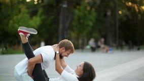 Портрет молодых активных пар имея потеху совместно в городе Привлекательная подруга скача на ее руки парней видеоматериал