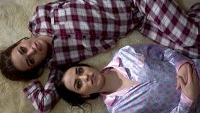 Портрет 2 молодых взрослых близнецов сестер лежа на мягком ковре мечтая и думая о том, что-то отношение сток-видео