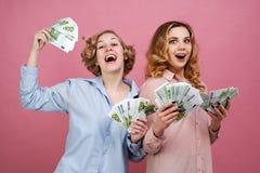 Портрет 2 молодых европейских девушек с евро наличных денег в руке и счастливом радостном выражении Они услажены с деньгами Стоковое Изображение RF