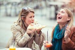 Портрет 2 молодых женщин есть пиццу outdoors Стоковое Изображение RF