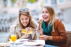 Портрет 2 молодых женщин есть пиццу outdoors Стоковая Фотография