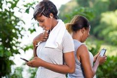 Портрет молодых женщин с мобильными телефонами стоковое изображение