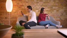 Портрет молодых кавказских друзей сидя спина к спине на софе со смартфонами в домашней атмосфере сток-видео