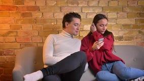 Портрет молодых кавказских пар сидя на софе наблюдая в смартфон и говоря друг с другом в доме видеоматериал