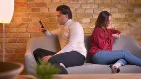 Портрет молодых кавказских пар сидя спина к спине на софе со смартфонами в домашней атмосфере акции видеоматериалы
