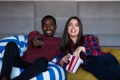 Портрет молодых пар сидя на софе смотря фильм с выражением на их сторонах стоковое фото