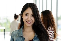 Портрет молодых привлекательных азиатских творческих женщины или дизайнера усмехаясь и смотря камеру стоковое изображение