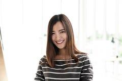 Портрет молодых привлекательных азиатских творческих женщины или дизайнера усмехаясь и смотря камеру в современном офисе чувствуя стоковые изображения rf