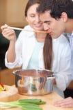 Портрет молодого человека пробуя соус его супруги Стоковое Изображение RF