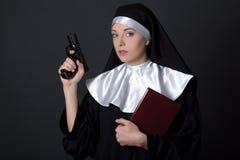 Портрет монашки молодой женщины с библией и оружием над серым цветом Стоковые Изображения