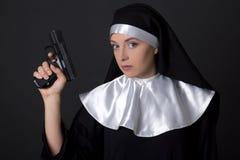 Портрет монашки молодой женщины с оружием над серым цветом Стоковое Фото