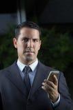 Портрет молодого латинского бизнесмена используя сотовый телефон Стоковое фото RF