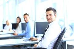 Портрет молодого бизнесмена в офисе с коллегами Стоковое фото RF