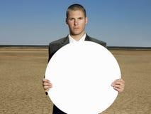 Портрет молодого бизнесмена держа пустой знак Стоковое Изображение