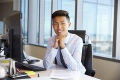 Портрет молодого бизнесмена на столе офиса используя компьютер Стоковая Фотография