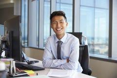 Портрет молодого бизнесмена на столе офиса используя компьютер Стоковое фото RF
