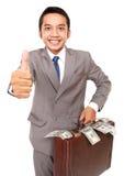 Портрет молодого бизнесмена нося сумку вполне денег Стоковое Изображение