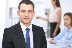 Портрет молодого бизнесмена против группы в составе бизнесмены на встрече Стоковые Изображения