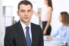 Портрет молодого бизнесмена против группы в составе бизнесмены на встрече Стоковые Фотографии RF