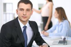 Портрет молодого бизнесмена против группы в составе бизнесмены на встрече Стоковые Изображения RF