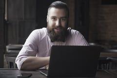 Портрет молодого бородатого бизнесмена работая с компьтер-книжкой Suc Стоковое Фото