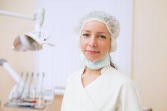 Портрет молодого женского дантиста, стоя в зубоврачебном офисе усмехаясь и смотря камеру Стоковая Фотография RF