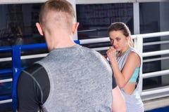 Портрет молодого женского боксера в тренировке sportswear с человеком Стоковая Фотография