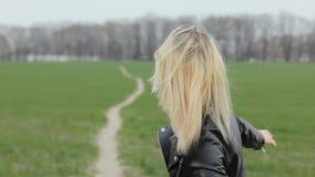 Портрет молодого женского коромысла усмехаясь и смотря камеру на зеленом поле сток-видео