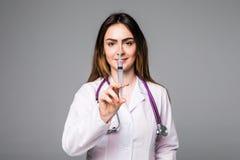 Портрет молодого женского доктора усмехаясь с шприцем в ее руке Портрет красивого доктора женщины на сером цвете Стоковая Фотография