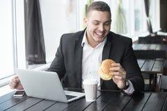 Портрет молодого жизнерадостного бизнесмена есть гамбургер пока wo Стоковые Изображения