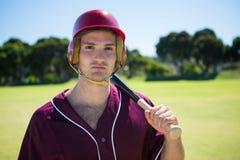 Портрет молодого игрока держа бейсбольную биту стоковые фото