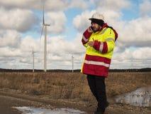 Портрет молодого инженера говоря мобильным телефоном outdoors в шлеме и отражательной куртке Стоковое Изображение RF