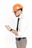 Портрет молодого инженера по строительству и монтажу в оранжевом шлеме с папкой на белой предпосылке Стоковые Изображения