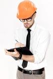 Портрет молодого инженера по строительству и монтажу в оранжевом шлеме с папкой на белой предпосылке Стоковые Изображения RF